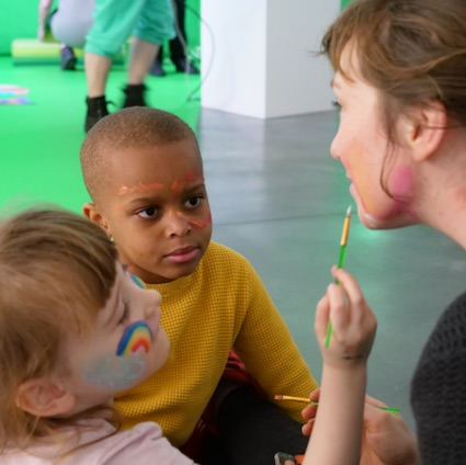 Facilitator Katriona Beales having her face painted by two children, at one of Autograph's Free Family SEND Workshops
