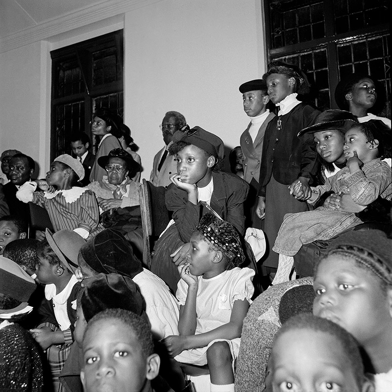 A large group of young and elderly people sitting together. They are all looking away from the camera.