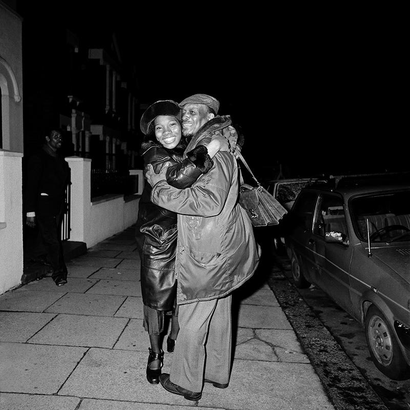 Two smiling people hug on a street at night next to a car. A passerby walks behind them.