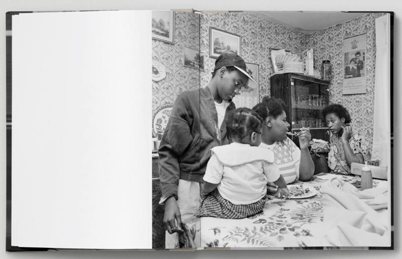 A spread from Roy Mehta's book Revival: London 1989-1993. Two people sit on a table eating food with two children.