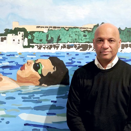 Autograph's Director Mark Sealy stood in front of a painting by Sharif Persaud. The painting is of a man floating in the seaAutograph's Director Mark Sealy stood in front of a painting by Sharif Persaud. The painting is of a man floating in the sea