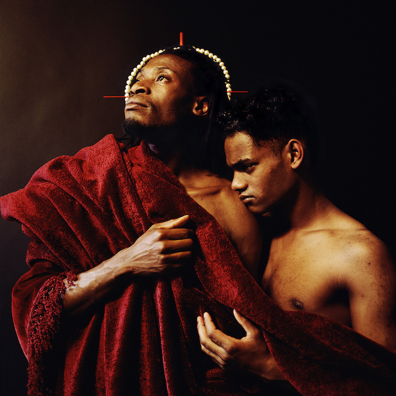 Two men wrapped in a red blanket. One is wearing a pearl crown and looking upward, while the other rests his head on the firsts shoulder.