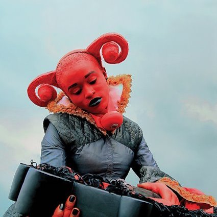 A lady with her skin painted red. She has a red headdress that curls out either side of her head and is holding something.