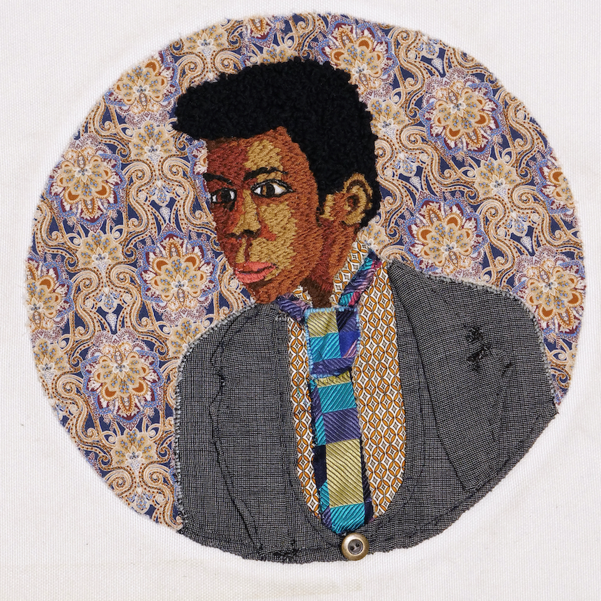 Embroidery of a man with grey suit jacket and blue tie, by member of Headway East London.