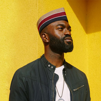 Photograph of Inua Ellams by Caleb Femi. Ellams looks towards the right hand corner of the image, appearing to be gazing in to the distance. He is bearded and against a bright yellow wall.