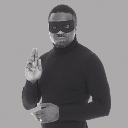 A black and white photograph of the artist Faisal Abdu'Allah dressed in a black poloneck. He has on an apparent superhero eye mask and is holding up two of his fingers on his right hand in an almost religious pose. His left hand is crossed gently across his body.