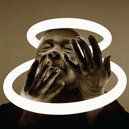 Sepia-toned photograph of a man with his hands up around his face. He is surrounded by two halo-like glowing circles and has his eyes half closed as if he were bathing in the light they provide.