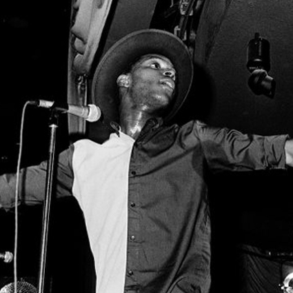 A black and white photograph of a man on stage performing in to a microphone. His hat is tilted upwards and his shirt is split in to two different colours. Sweat is visible on his neck from the exertion of performing.