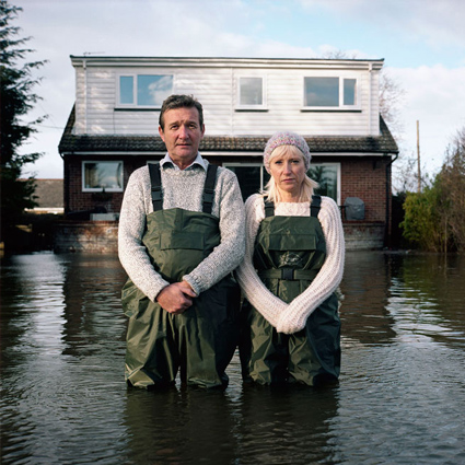 Two people look outwards while standing up to their knees in what looks like a lake. Their house behind them is also partially submerged in water. They are wearing matching green overalls. Photograph from Gideon Mendel's Drowning World