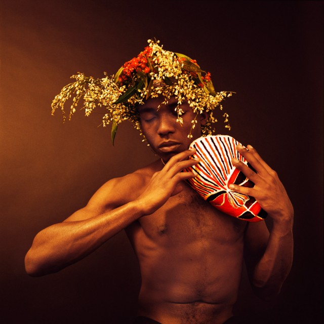 A man stood holding a mask on his shoulder. His eyes are closed and he is wearing a headdress made of flowers.