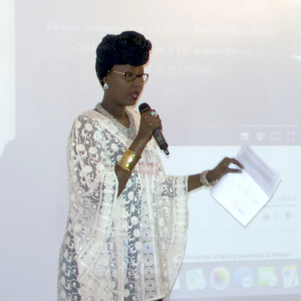 A woman with a microphone carrying paper gestures to the audience.
